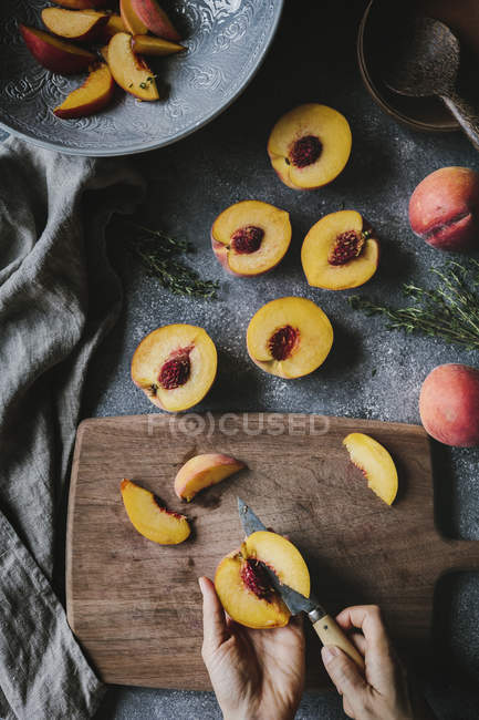 Female hands slicing peaches — Stock Photo