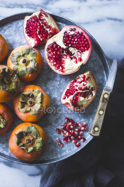 Pomegranate and Persimmons on tray — Stock Photo