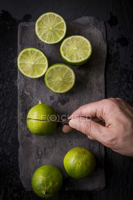 Mann schneiden frische reife Limetten — Stockfoto