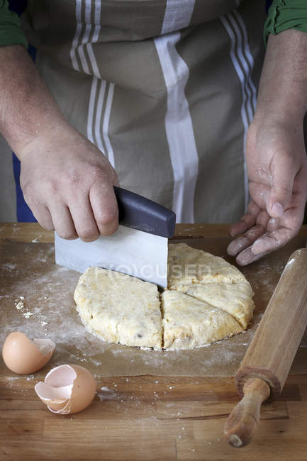 Man slicing raw dough — Stock Photo
