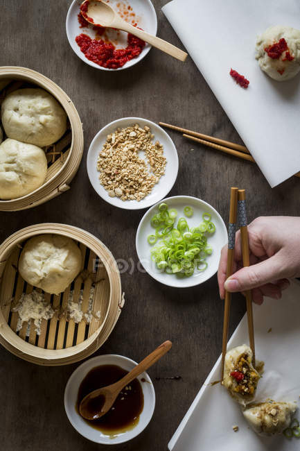 Female hand with chopsticks placing dumpling — Stock Photo
