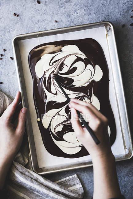 Жінка плавлення білий і чорний шоколад — стокове фото