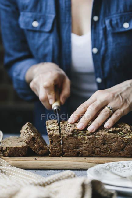 Donna che affetta il pane vegan — Foto stock