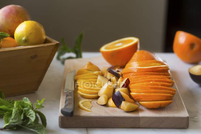 Naranjas frescas de corte en el tablero de corte - foto de stock