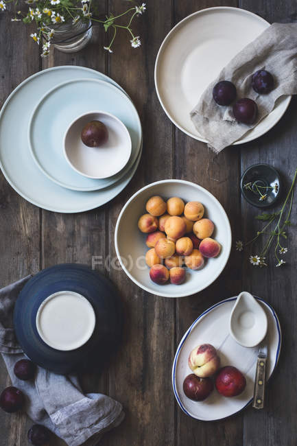 Peaches and plums on ceramic plates — Stock Photo