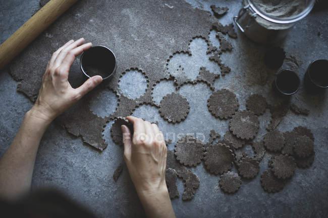 Female hands cutting buckwheat dough — Stock Photo