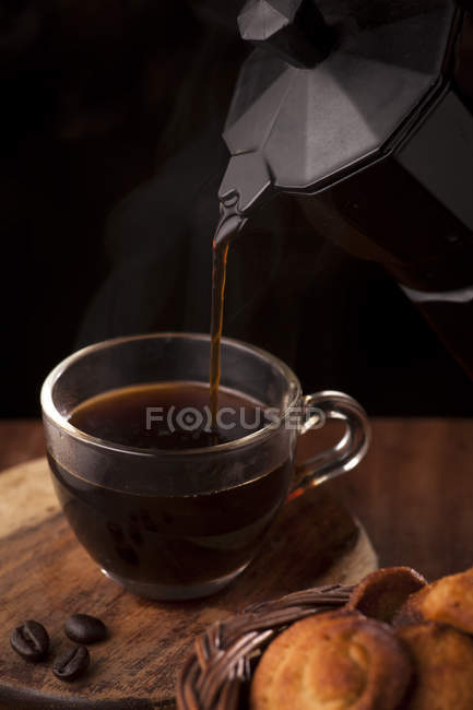 Pouring cup of coffee and cookies — Stock Photo