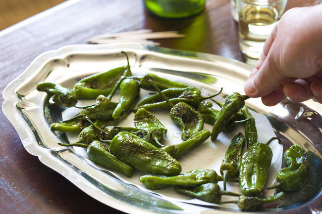 Hand touching fresh padron peppers — Stock Photo