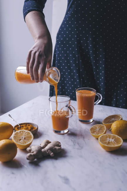 Woman pouring orangeand carrot juice — Stock Photo