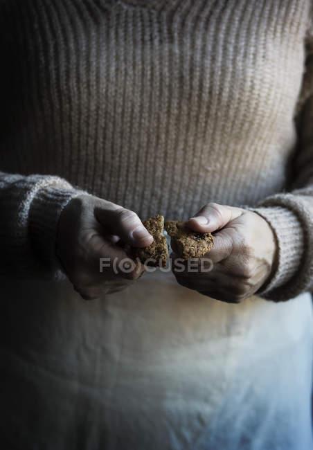 Donna che tiene biscotto rotto — Foto stock