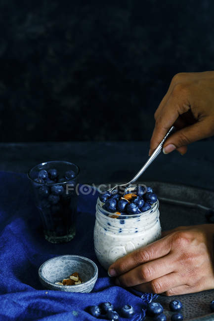 Woman eating Blueberry yogurt — Stock Photo