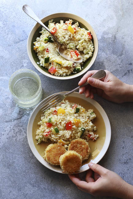 Female hands holding plate with couscous — Stock Photo