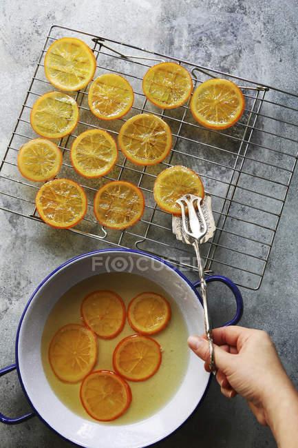 Mano femminile immissione arance candite — Foto stock