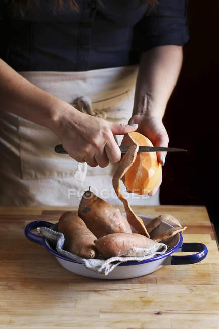Mujer naranja pelar batatas - foto de stock