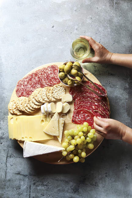 Cheese board with sausages and salami — Stock Photo