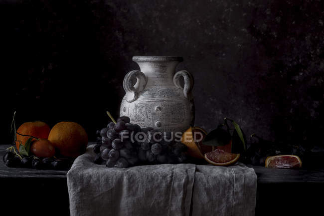 Grapes and oranges with vintage vase — Stock Photo