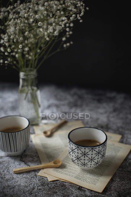 Cups of espresso coffee with book pages — Stock Photo