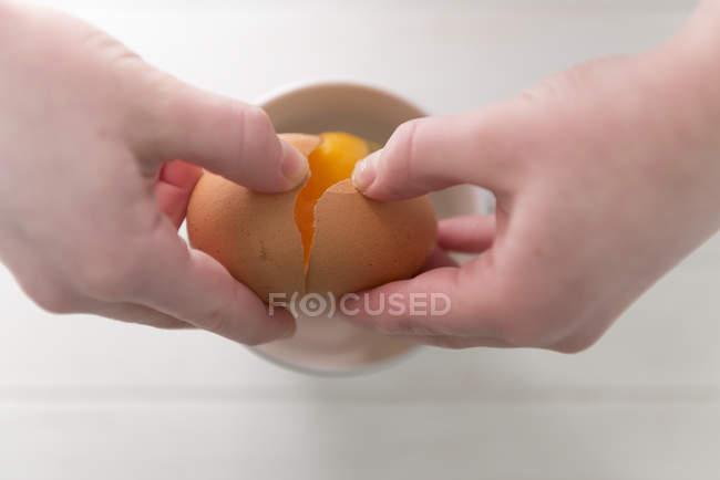Жіночих рук розтріскування в миску яйця — стокове фото