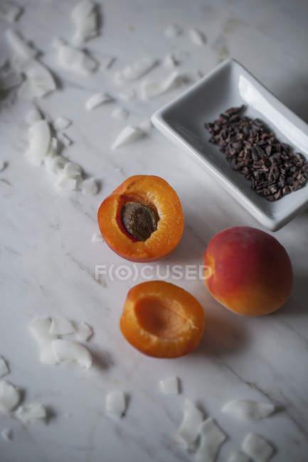 Albaricoques frescos y semillas de cacao - foto de stock