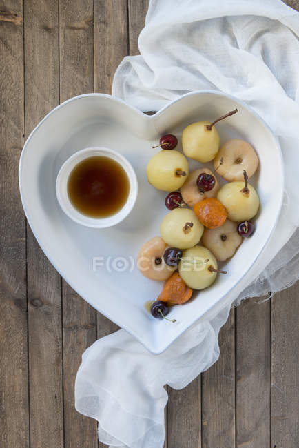 Poached fruits in heart shaped dish — Stock Photo