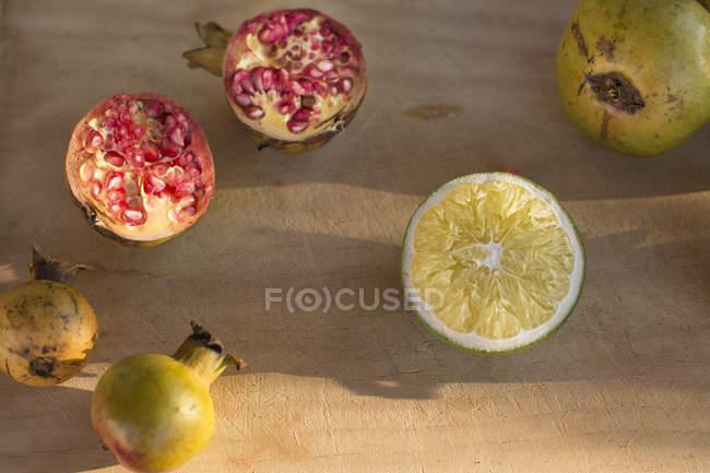 Corte a romã com metade do limão — Fotografia de Stock