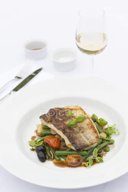Gebratener Fisch auf einem Gemüsebett — Stockfoto