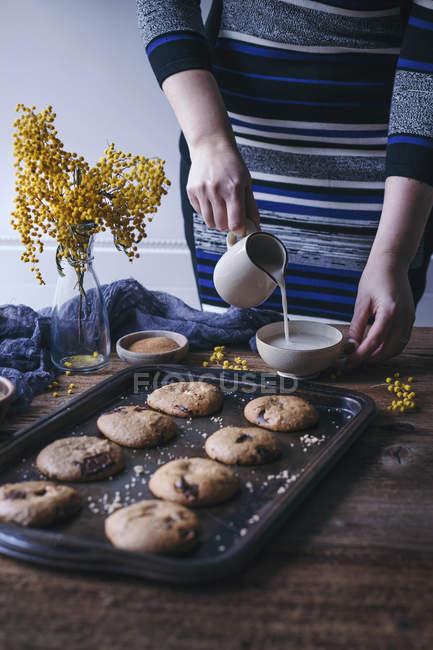 Женщина наливает миндальное молоко в чашку — стоковое фото