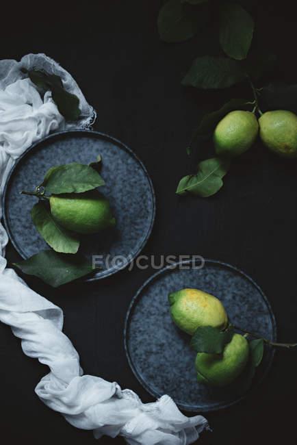 Citrons non mûrs sur des assiettes — Photo de stock