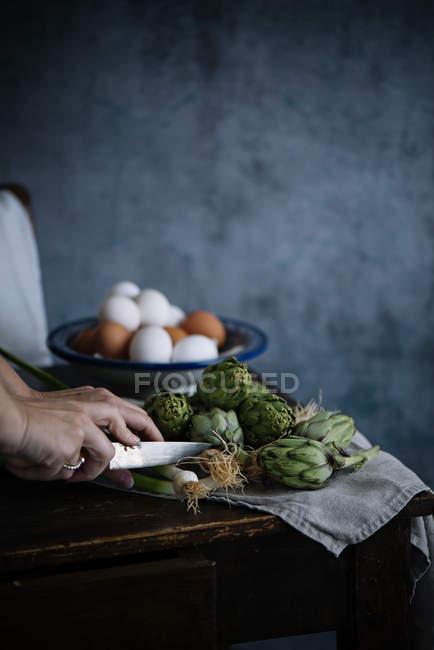 Женщина режет артишоки и скальоны — стоковое фото
