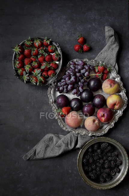 Fruits and berries on platter and bowls — Stock Photo