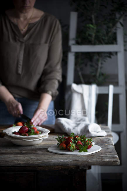 Woman cutting strawberries — Stock Photo