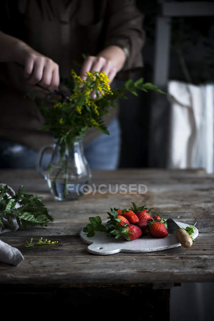 Woman cutting rustic flowers — Stock Photo