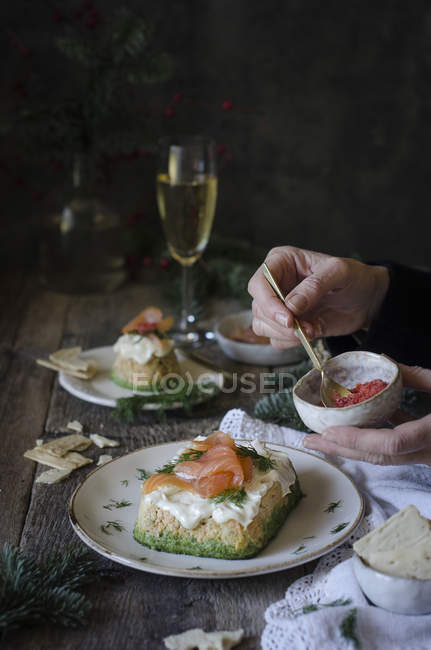 Woman Garnishing salmon mini cakes — Stock Photo