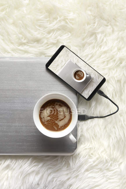 Cup of coffee and cell phone — Stock Photo