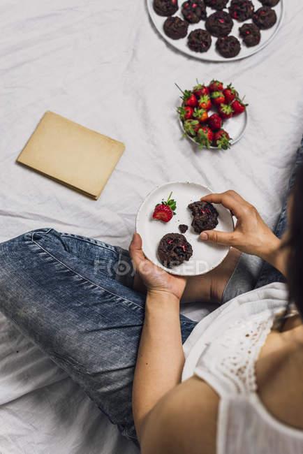 Женщина ест печенье и клубники — стоковое фото