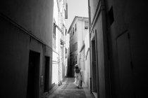 Mulher caminhando no caminho cercado por paredes — Fotografia de Stock