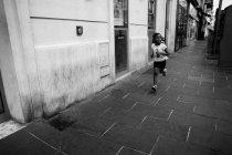 Girl running at sidewalk in urban street — Stock Photo
