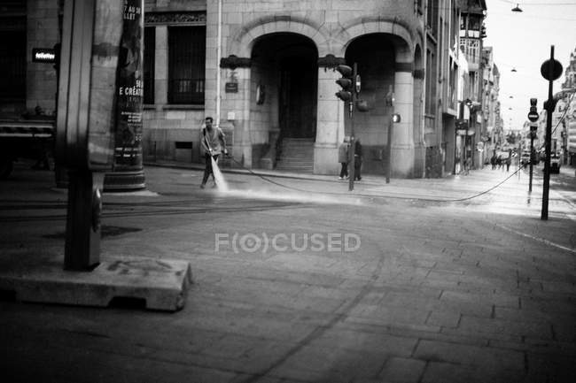 Hombre limpieza calle con manguera de agua - foto de stock