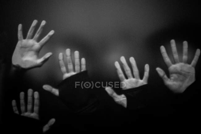 Hands of models on transparent surface — Stock Photo