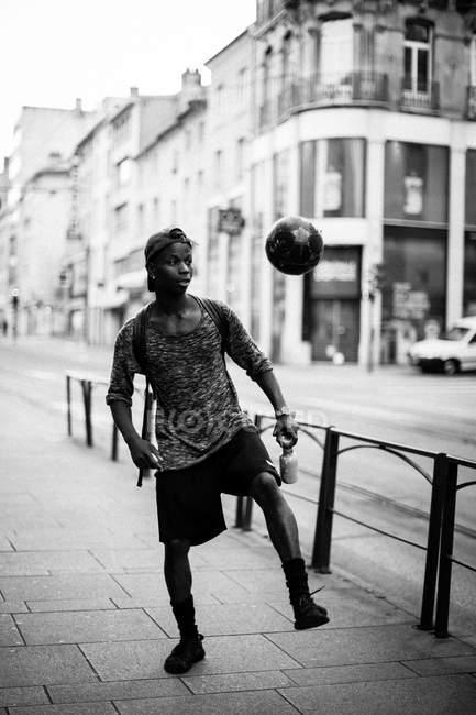 Homem chutando bola de futebol na rua urbana — Fotografia de Stock