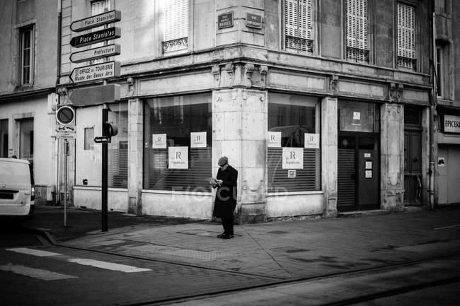Mann in schwarzem Mantel steht an Kreuzung — Stockfoto