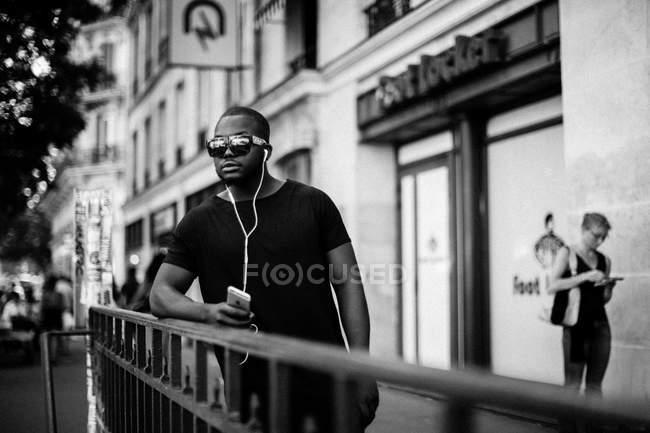 Людиною, в окулярах, слухати музику в навушниках — стокове фото