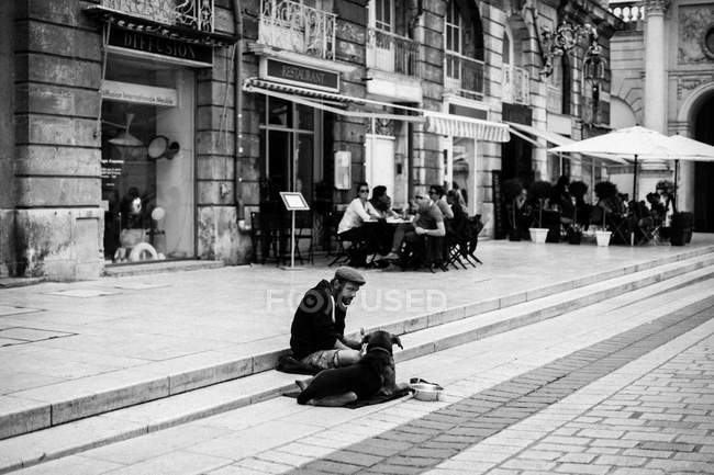Man sitting on stairs near dog — Stock Photo