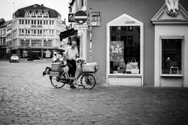 Homme avec vélo près du magasin — Photo de stock