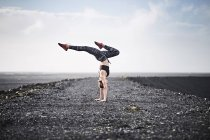 Woman doing handstand on deserted road — Stock Photo