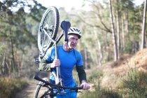 Мужчина носит с собой горный велосипед — стоковое фото