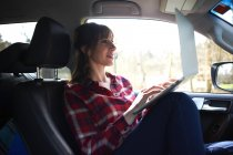 Woman sitting in car and using laptop — Stock Photo