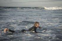 Homme en wetsuit prépare à surfer — Photo de stock