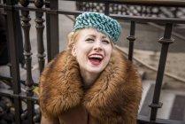 Frau sitzt lachend am Geländer — Stockfoto