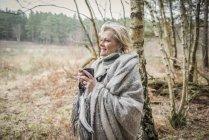 Леди, завернутый в одеяло, наслаждаясь чашкой чая — стоковое фото